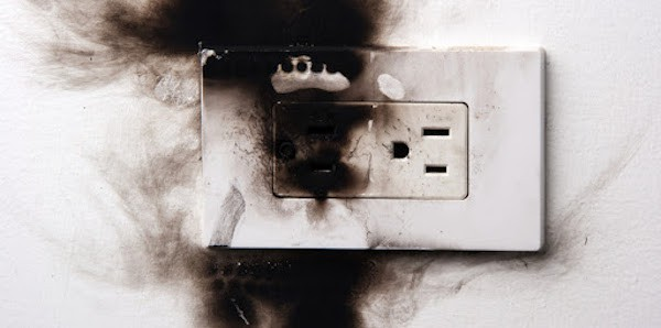 electrical outlet that's singed after aluminum wiring inside it caught fire and burned